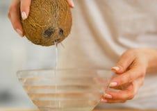 Closeupen på den hällande kokosnöten för den unga kvinnan mjölkar i platta Arkivfoto