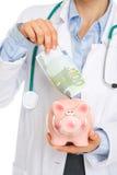 Closeupen på läkarundersökning manipulerar sätta 100 euros noterar I Royaltyfri Bild