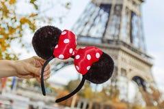 Closeupen på Minnie Mouse gå i ax i hand framme av Eiffeltorn Royaltyfria Bilder