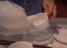 Closeupen på moment av kines häller te med begrepp av omsorg och sunt arkivfoto