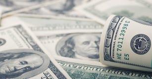 Closeupen rullade dollar hundra på för pengardollar för bakgrund amerikansk räkning Många sedel för USA 100 arkivbild