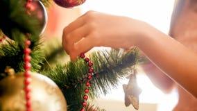 Closeupen sköt av den unga kvinnan som smyckar julgranen på morgonen fotografering för bildbyråer