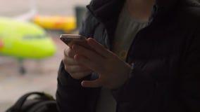Closeupen sköt av en ung kvinna som framme använder en smartphone av ett stort fönster på en flygplats stock video