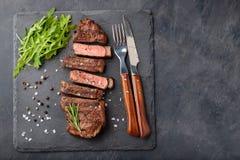 Closeupen som är klar att äta biffNew York köttraser av svarta Angus med örter, vitlök och smör på en sten stiger ombord _ royaltyfri fotografi