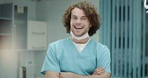 Closeupen som ler den karismatiska unga doktorn eller kirurger som ser raka till kameran, i ett sjukhusrum, doktorn har lager videofilmer