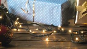 Closeupen tonade längd i fot räknat av färgrika babubles, julgåvor och glödande ljusa garlans på träbackgorund arkivfilmer