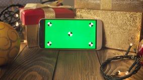 Closeupen tonade videoen 4k av den smarta telefonen på trätabellen dekorerade för julberöm Grön chromakeyskärm för lager videofilmer