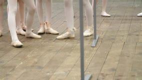 Closeupen unga ballerinaben i balettskor, pointes, i beigea body, utf?r ?vningar n?ra barren, p? ett gammalt lager videofilmer