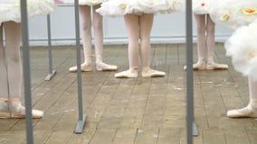 Closeupen unga ballerinaben i balettskor, pointes, i beigea body, vita ballerinakjolkjolar, utför övningar nära stock video