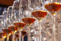Closeupexponeringsglas med konjakställningen i linje Nedanfört beskåda Konjak för whisky för begreppsdegustationandar, porto som  fotografering för bildbyråer