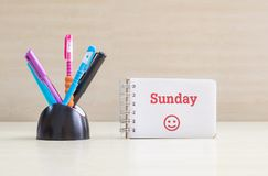 Closeupfärgpenna med det svarta keramiska skrivbordet som är rumsrent för penna och det röda söndag ordet i den vita sidan och ly Arkivfoto
