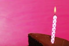 Closeupfödelsedagstearinljus i skiva av chokladcaken Fotografering för Bildbyråer