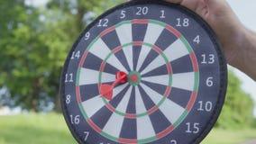 Closeupfaderhänder som rymmer pilar medan hans son som kastar pilar och bollen på en magnet i cirklarna Familjfritid lager videofilmer