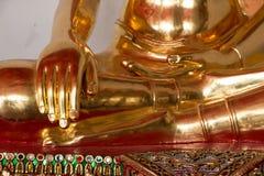 Closeupfingrarna av den guld- Buddhastatyn Arkivfoton