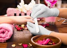 Closeupfingret spikar omsorg av manikyrspecialisten i skönhetsalong Royaltyfri Fotografi