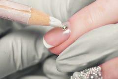 Closeupfingret spikar omsorg av manikyrspecialisten i skönhetsalong royaltyfri bild