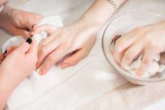 Closeupfingret spikar omsorg av manikyrspecialisten i skönhetsalong Pojkar för klart nagelband för manikyrist yrkesmässiga för Royaltyfri Bild