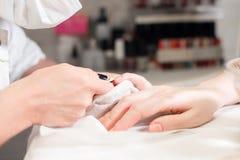 Closeupfingret spikar omsorg av manikyrspecialisten i skönhetsalong Pojkar för klart nagelband för manikyrist yrkesmässiga för Royaltyfria Bilder