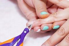 Closeupfingret spikar omsorg av manikyrspecialisten i skönhetsalong Sax för klart nagelband för manikyrist yrkesmässig för maniky royaltyfri foto
