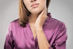 Closeupflicka med den öm halsen som trycker på hennes hals royaltyfri fotografi