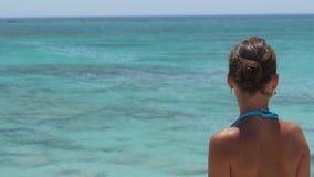 Closeupflicka som håller ögonen på havet stock video