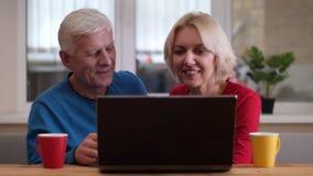 Closeupfors av åldriga lyckliga par genom att använda bärbara datorn med koppar med te på skrivbordet inomhus i en hemtrevlig läg lager videofilmer