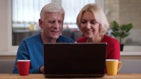Closeupfors av åldriga lyckliga par genom att använda bärbara datorn på skrivbordet med koppar med te inomhus i en hemtrevlig läg stock video