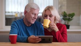 Closeupfors av åldriga lyckliga par genom att använda minnestavlan med koppar med te på skrivbordet inomhus i en hemtrevlig lägen arkivfilmer