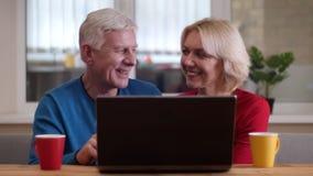 Closeupfors av åldriga lyckliga par som har en video appell på bärbara datorn med koppar med te på skrivbordet inomhus i en slags lager videofilmer