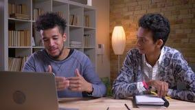 Closeupfors av afrikanska amerikanen och indiska manliga studenter som har en rolig diskussion tillsammans En använder på arkivfilmer