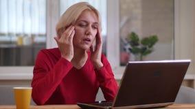 Closeupfors av den åldriga caucasian affärskvinnan som inomhus skriver på bärbara datorn och har en huvudvärk i en hemtrevlig läg arkivfilmer