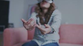 Closeupfors av den kvinnliga handinflyttningen utrymmet, medan genom att använda virtuell verklighetexponeringsglas hemma Flicka lager videofilmer