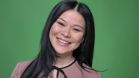 Closeupfors av den kvinnliga unga attraktiva asiatet vända att le glatt och att se rakt på kameran med bakgrund arkivfilmer