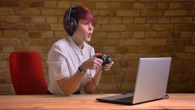 Closeupfors av den kvinnliga videopd bloggeren för ung attraktiv hipster som spelar videospel genom att använda den modiga konsol royaltyfri foto