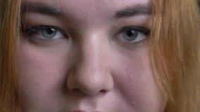 Closeupfors av den unga attraktiva överviktiga kvinnliga framsidan med gråa ögon som ser raka på kameran i begrundande stock video