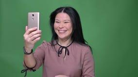 Closeupfors av den unga attraktiva asiatiska kvinnlign med svart hår som har en video appell på telefonen med isolerad bakgrund arkivfilmer