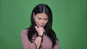 Closeupfors av den unga attraktiva asiatiska kvinnlign som är fundersam och framme fixar hennes hår av kameran lager videofilmer