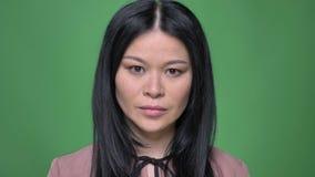 Closeupfors av den unga attraktiva asiatiska kvinnlign som framme fixar hennes hår av kameran med bakgrund som isoleras på gräspl arkivfilmer