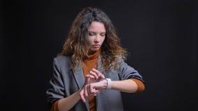 Closeupfors av den unga attraktiva caucasian affärskvinnan som kontrollerar tid på hennes armklocka med bakgrund som isoleras på arkivfoton