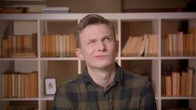 Closeupfors av den unga attraktiva caucasian visningtungan och framställning för manlig student av roliga ansiktsuttryck som ser lager videofilmer