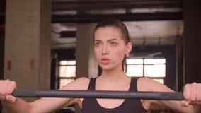Closeupfors av den unga attraktiva idrottsman nenkvinnlign som går och får klar att lyfta vikter med beslutsamhet i idrottshallen stock video