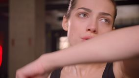 Closeupfors av den unga attraktiva idrottsman nenkvinnlign som inomhus utarbetar och svettas i idrottshallen lager videofilmer