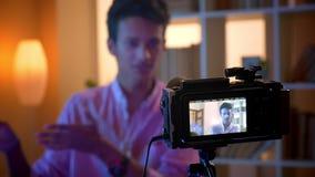 Closeupfors av den unga attraktiva indiska manliga bloggeren som talar på kamera och inomhus gör en gest i en hemtrevlig lägenhet stock video
