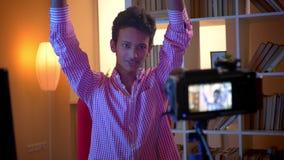 Closeupfors av den unga attraktiva indiska manliga bloggeren som talar på kamera och inomhus gör en gest i en hemtrevlig lägenhet arkivfilmer