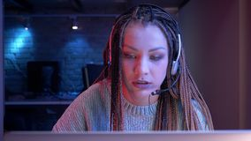 Closeupfors av den unga attraktiva kvinnliga bloggeren med dreadlocks i hörlurar som spelar levande videospel och tryckning
