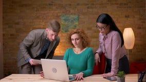 Closeupfors av den unga caucasian affärskvinnan som arbetar på bärbara datorn och diskuterar data med att le för två kollegor arkivfilmer