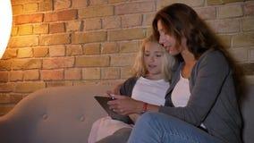 Closeupfors av den unga caucasian modern och hennes lilla nätta blonda flicka som tillsammans använder minnestavlan, medan sitta  arkivfilmer