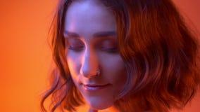 Closeupfors av den unga gladlynta caucasian flickan med härlig makeup som ler och vänder till kameran med neon rött arkivfilmer