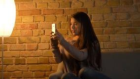 Closeupfors av den unga gulliga caucasian kvinnlign som använder telefonen och tar selfies, medan vila på soffan i en slags tvåsi arkivfoton