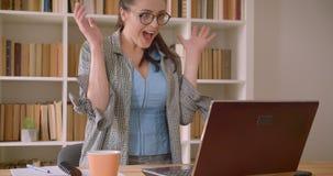 Closeupfors av den unga lyckade caucasian affärskvinnan i exponeringsglas genom att använda bärbara datorn och fira i arkivet stock video